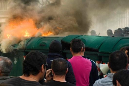 Antidisturbios e Mariñeiros separados por unha barricada de catro contenedores